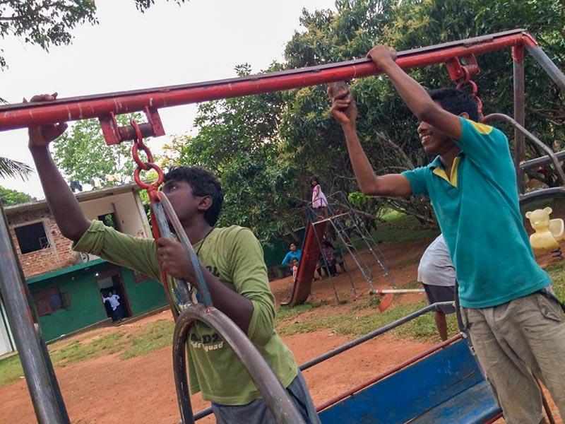 twee jongen knappen het speeltoestel op
