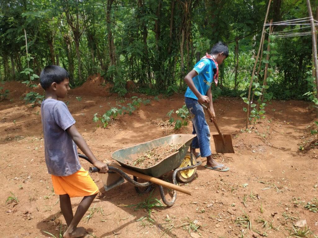 Jongens met kruiwagen en schep