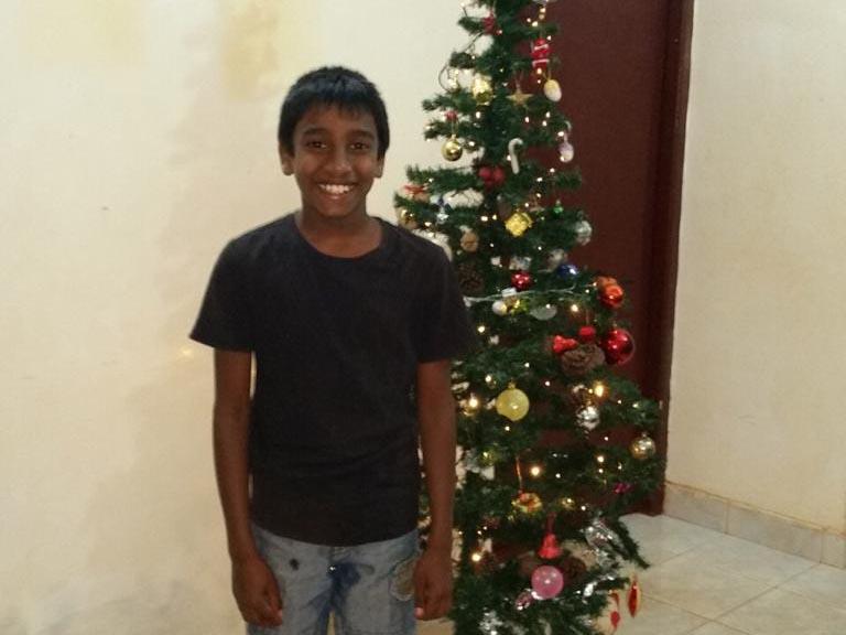 jongen poseert bij de kerstboom