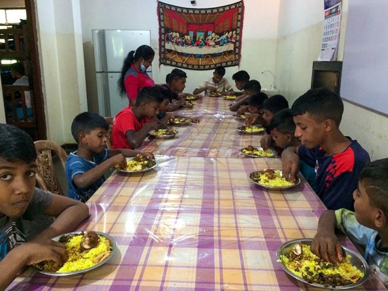 De jongens zitten aan tafel te eten